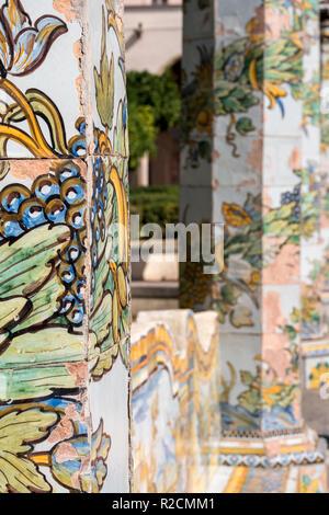 Piliers carrelés colorés et banc dans le jardin du cloître au monastère Santa Chiara Via Santa Chiara, à Naples, Italie. Banque D'Images