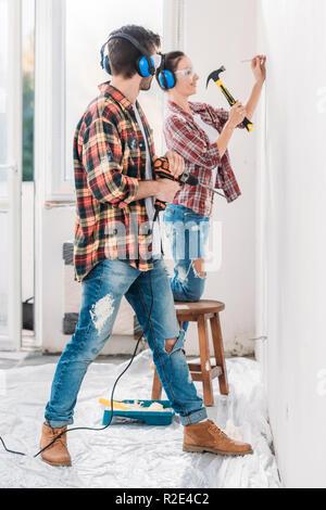 Side view of young man et à sourire à l'épouse de marteau clou dans nouvel appartement Banque D'Images