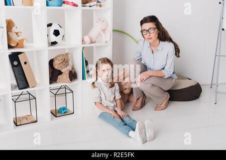 Femme soutien psychologue enfant déprimé pendant qu'elle assis sur le plancher et looking at camera Banque D'Images