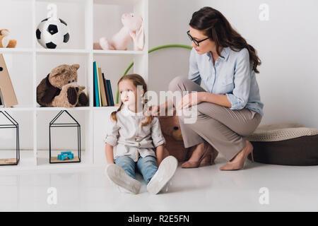 Femelle adulte soutien psychologue enfant déprimé pendant qu'elle sitting on floor Banque D'Images