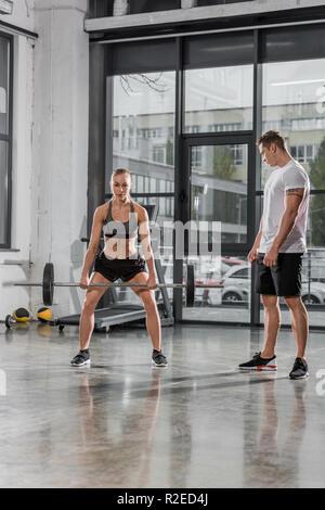 Formateur à la sportive l'entraînement avec haltères longs in gym Banque D'Images