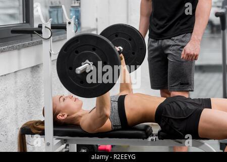 Image recadrée de trainer près de la sportive couché sur banc et levage barbell in gym Banque D'Images