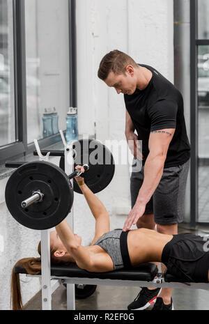Formateur à la sportive à couché sur banc et levage barbell in gym Banque D'Images