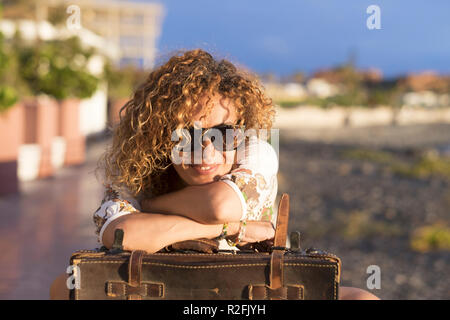 Belle et joyeuse dame d'âge moyen cheveux blonds détendu après le voyage dans l'air extérieur sur la côte. transport et de destination pour les personnes de race blanche concept nice. vintage bagages et de vie moderne Banque D'Images