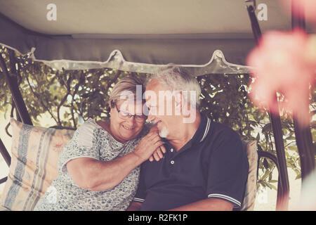 Belle paire de très beaux hauts de race blanche âgé de 70 ans s'asseoir à la maison en plein air s'amusant avec des sourires et rire. heureuse vie ensemble pour toujours dans l'amour et de profiter de temps à la retraite. L'accent sur l'homme Banque D'Images