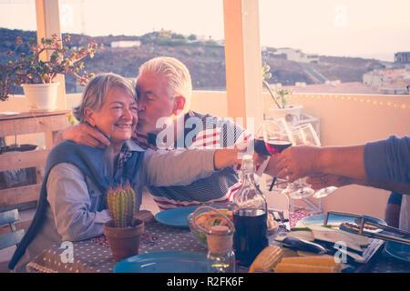 Groupe d'amis adultes âgés de hauts en train de dîner et faisant partie agréable moment dans le toit-terrasse piscine avec du vin et de l'alimentation. s'amuser et baiser pendant le coucher de soleil magnifique avec rétro-éclairage et vue incroyable sur la mer et sur d'autres toits. Banque D'Images