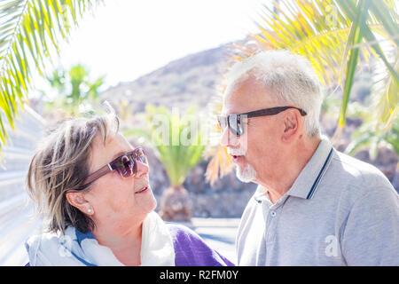 Joli couple heureux des adultes aînés restez ensemble sous le soleil avec hug et belle vie quotidienne. togetner lunettes de soleil et de vacances parlant entre eux avec bonheur Banque D'Images