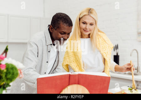 Heureux couple interracial avec cuisine livre de cuisine ensemble à dîner Banque D'Images