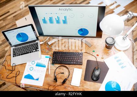 Vue de dessus sur le lieu de travail avec différents tableaux de statistiques ou d'analyse, les captures d'écran et dessins papier