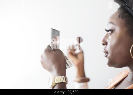 En appliquant le maquillage femme miroir compact Banque D'Images