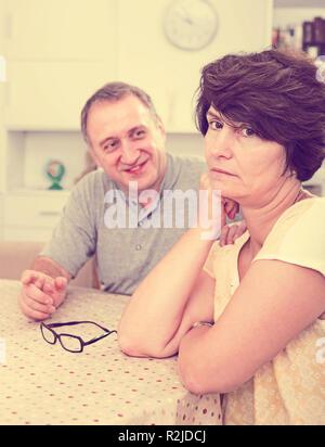 Triste femme adulte aux prises avec des problèmes familiaux avec son partenaire à l'intérieur