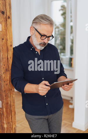 Homme avec une barbe et des lunettes debout appuyé contre un pilier en bois d'intérieur de la lecture d'un tablet pc Banque D'Images