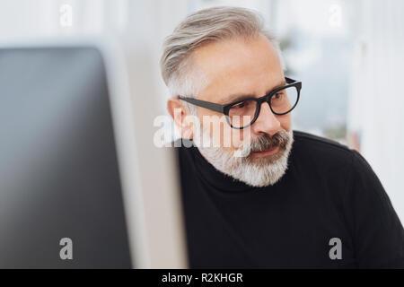 Businessman looking attentivement le côté regardant quelque chose avec intérêt comme il travaille à un moniteur de bureau Banque D'Images