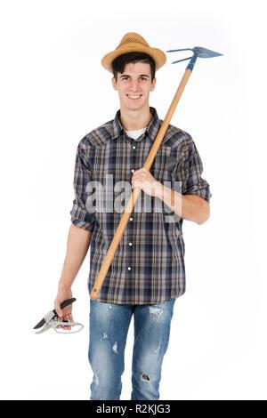 Jeune agriculteur avec cisailles et hoe en mains, il porte un chapeau de paille, chemise à carreaux et bottes de caoutchouc vert Banque D'Images