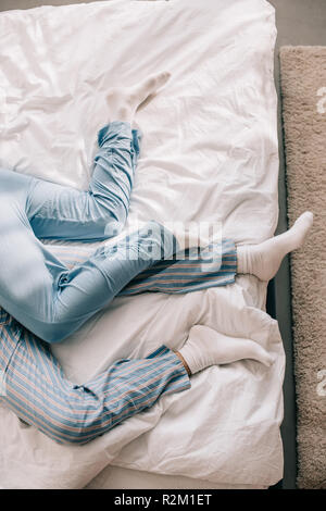 Cropped shot of couple en pyjama relaxing in bed in morning Banque D'Images