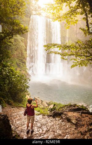 Un touriste photographie la Misty Misol Ha cascades au Chiapas, Mexique. Banque D'Images