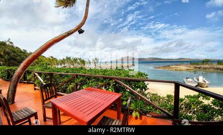 Table rouge et des chaises sur terrasse sur plage de sable blanc, deux bateaux à la mer, les Fidji Banque D'Images