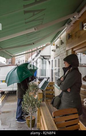 Bewdley, UK. 20 novembre, 2018. Météo France: sur une froide journée de novembre, amèrement avec les vents et averses soudaines de Brisk, folk sont désireux de chercher refuge et voir ce qui est offert dans les bureaux de l'hôtellerie. Une personne quitte, attente de la pluie à l'aise tandis qu'un couple avec parapluie vérifier le menu à l'extérieur. Credit: Lee Hudson/Alamy Live News