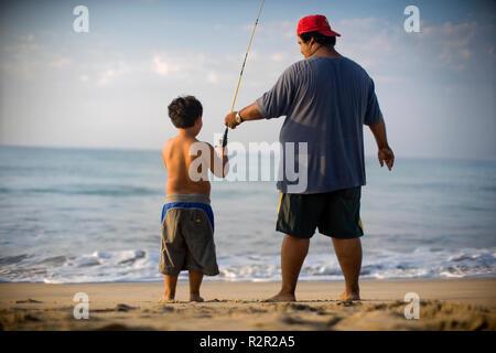 Un homme enseigne à son fils la loi de la pêche, près de la mer. Banque D'Images