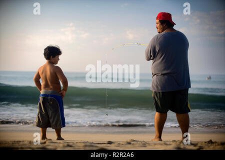Vue arrière d'un homme près du littoral pêche tandis qu'un petit garçon le regarde. Banque D'Images