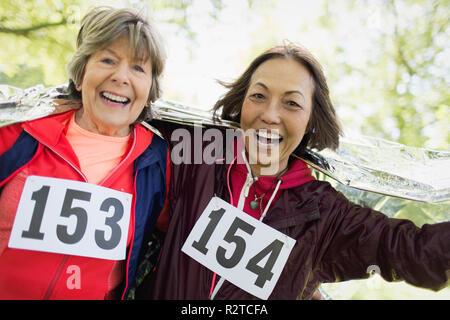 Portrait souriant, confiant senior femmes sports race de finition, enveloppé dans une couverture thermique Banque D'Images