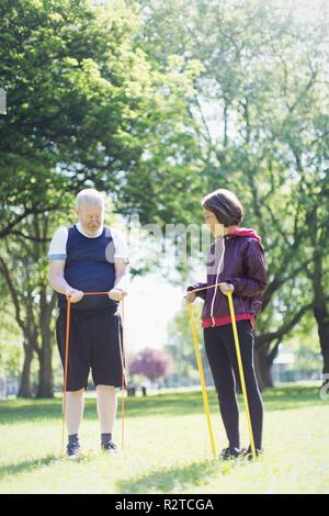 Senior couple exercising, stretching avec bandes de résistance à sunny park Banque D'Images