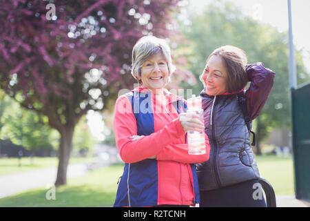 Portrait confiant senior female runner les amis de l'eau potable dans park Banque D'Images