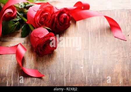 Belles roses rouges avec ruban de soie sur fond de bois avec copyspace. Bouquet de fleurs Décoration pour la Saint-Valentin. Banque D'Images