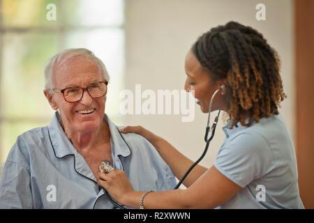 Smiling senior homme ayant son rythme cardiaque écouté par une infirmière. Banque D'Images
