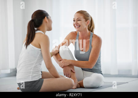 Souriante jeune femme prenant une pause à partir d'une classe de yoga. Banque D'Images