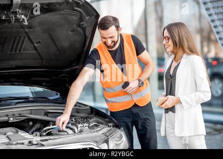 Beau service worker consulting ou fournir une assistance technique de la voiture cassée à la businesswoman outdoors Banque D'Images
