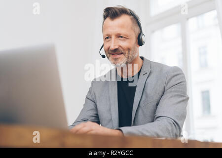 Portrait of mature man wearing headset travaillant dans un centre d'appel Banque D'Images