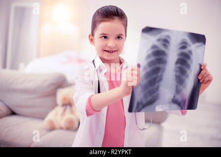 Aux yeux sombres cute girl wearing white jacket holding x-ray de poumons Banque D'Images