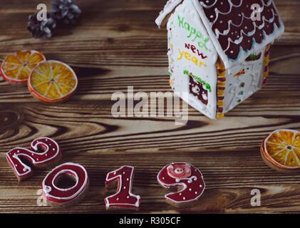 Carte de Noël sur fond rouge bois d'épice numéros 2019 avec des tranches d'orange et blanc avec une maison, une fenêtre de toit brun et l'i Banque D'Images