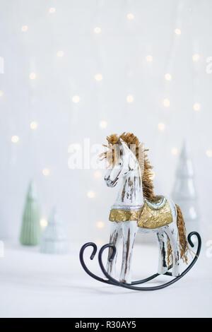 Jouet à bascule Cheval de bois avec des arbres de Noël et les lumières led garland sur l'arrière-plan. Orientation verticale.