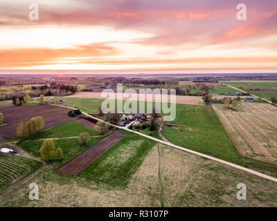 Drone aérien Photo d'un village entouré de prairies dans un beau soir de printemps en couleurs avec coucher de soleil sur elle Banque D'Images