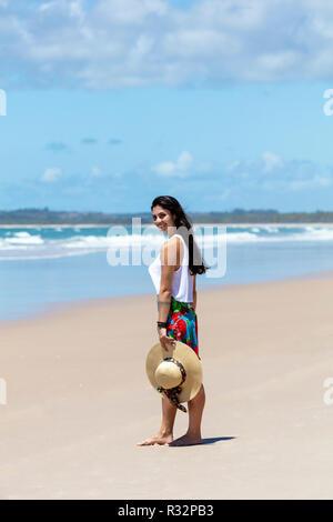 Une belle jeune femme dans une jupe, haut blanc et chapeau de paille sur une plage de sable blanc, palmier dans les tropiques