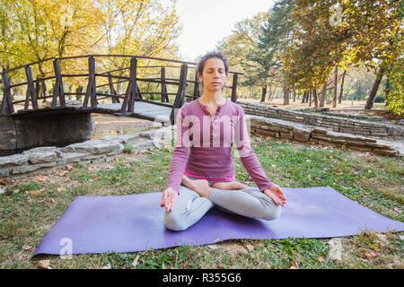 Santé de la jeune belle femme pratiquant le yoga et la méditation en posture du lotus Padmasana, exercice, assis sur le Tapis de fitness dans le parc, au jour d'automne.