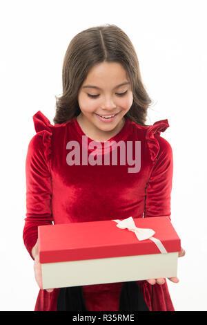 Kid little girl in élégante robe curly hairstyle attente boîte-cadeau. Enfant heureux de déballer son cadeau. Petite fille mignonne reçu cadeau de vacances. Ce qui est à l'intérieur. Meilleurs jouets et cadeaux de Noël pour les enfants.