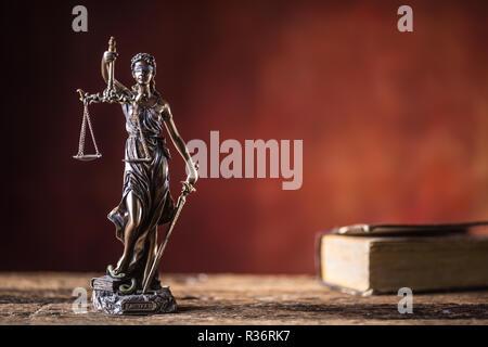 Dame Justicia tenant un sabre et l'échelle figurine en bronze avec livre sur table en bois.