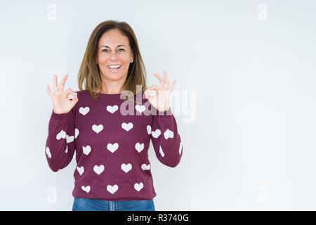 Belle femme d'âge moyen portant sur pull coeur fond isolé vous détendre et souriant avec les yeux fermé faisant le geste de la méditation avec les doigts. Yo Banque D'Images