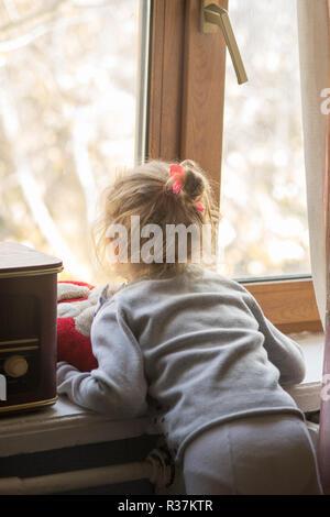 Kid regarde par la fenêtre, voir de l'arrière. Banque D'Images