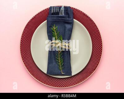 De Noël et du nouvel an, plat de service, la plaque grise sur plaque rouge, avec fourchette et couteau et serviette bleu avec la direction générale de l'arbre de Noël à fond rose Banque D'Images