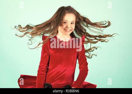 Sourire petite fille avec des cheveux volants sur fond bleu, la mode. Enfant smiling with long brunette hairstyle en robe rouge. Salon de concept. Soins capillaires, salon de coiffure, salon de coiffure. Punchy tendance pastel Banque D'Images