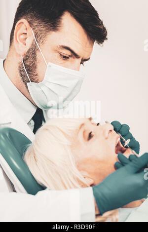 Au cours de l'examen. Femme âgée en gardant la bouche ouverte pendant que l'examen de médecin professionnel womans dents avec une aide d'instruments dentaires Banque D'Images