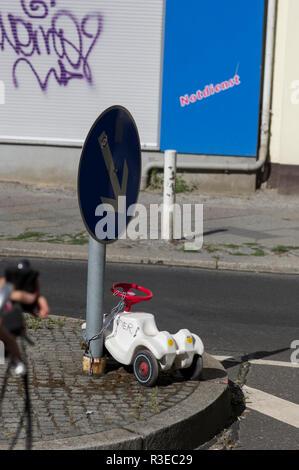 Une automobile en plastique blanc enchaîné à un poteau indicateur sur la rue à Berlin, en Allemagne, des graffitis sur les murs à l'arrière-plan Banque D'Images