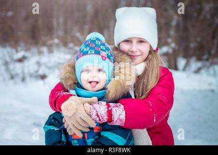 Petite fille épouse son frère dans la forêt d'hiver Banque D'Images