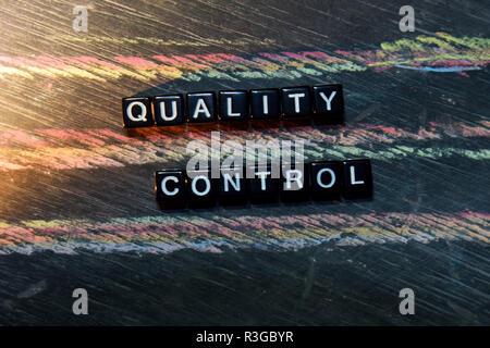 Le contrôle de qualité sur des blocs de bois. Cross image traitée avec tableau noir l'arrière-plan. L'inspiration, d'éducation et de motivation concepts Banque D'Images