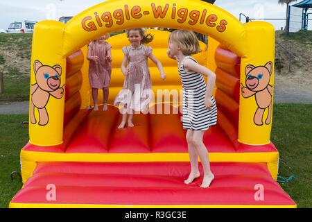 Trois enfants âgés de 4, 6, 8 ans, jouant / bouncing en toute sécurité sur un château gonflable gonflable dans un café / restaurant jardin. (98) Banque D'Images