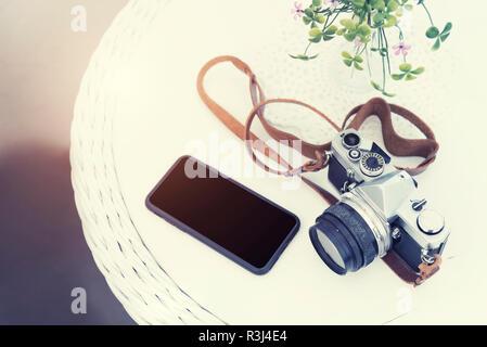 Vie, les voyages et la technologie concept. Vintage camera avec mobile sur table avec copie gratuite de l'espace. Vintage et rétro en toile de fond. Photo pour ajouter du texte m Banque D'Images